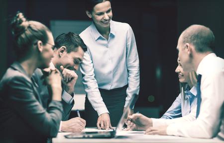 Photo pour business, technology and office concept - smiling female boss talking to business team - image libre de droit