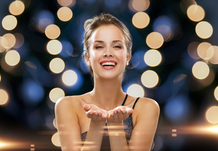 Foto de people, holidays, advertisement and luxury concept - laughing woman in evening dress holding something imaginary over night lights background - Imagen libre de derechos