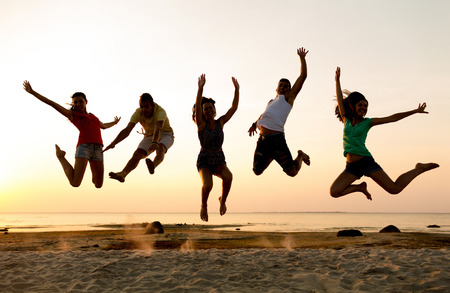 Photo pour friendship, summer vacation, holidays, party and people concept - group of smiling friends dancing and jumping on beach - image libre de droit