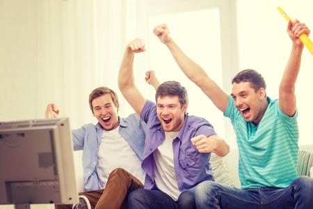 Photo pour friendship, sports and entertainment concept - happy male friends with vuvuzela watching sports on tv - image libre de droit