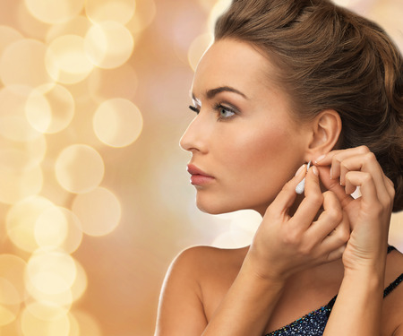 Photo pour people, holidays, christmas and glamour concept - close up of beautiful woman wearing earrings over beige lights background - image libre de droit