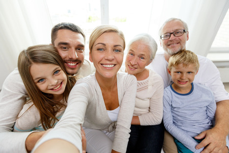 Foto de family, happiness, generation and people concept - happy family sitting on couch and making self portrait with camera or smartphone at home - Imagen libre de derechos