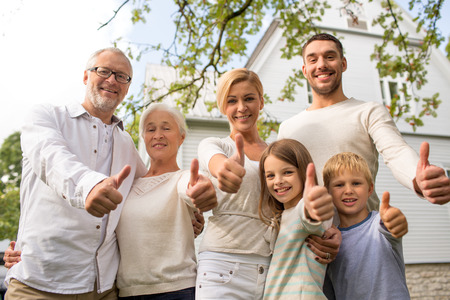 Foto de family, happiness, generation, home and people concept - happy family standing in front of house and showing thumbs up outdoors - Imagen libre de derechos