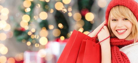 happiness, winter holidays and people concept - smiling young woman in hat and scarf with red shopping bags over christmas tree backgroundの写真素材