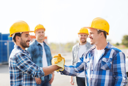 business, building, teamwork, gesture and people concept - group of smiling builders in hardhats greeting each other with handshake outdoors