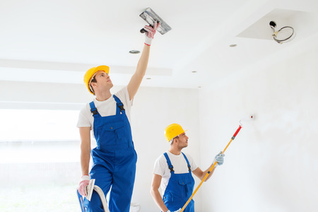 Photo pour business, building, teamwork and people concept - group of builders in hardhats with plastering tools indoors - image libre de droit
