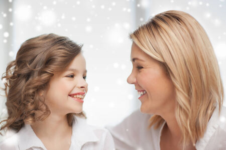 people, motherhood, family, winter and adoption concept - happy mother and daughter talking