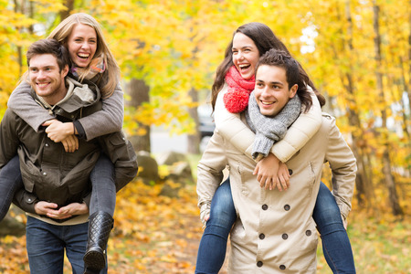 Photo for love, friendship, family and people concept - smiling friends having fun in autumn park - Royalty Free Image