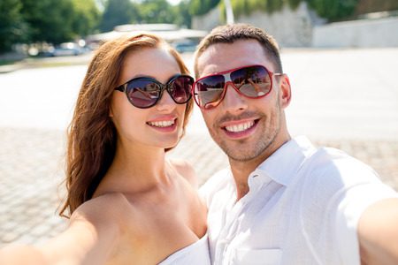 love, wedding, summer, dating and people concept - smiling couple wearing sunglasses making selfie in cityの写真素材