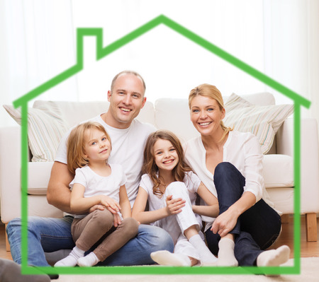 Foto de family, children, accommodation and home concept - smiling parents and two little girls at home behind green house symbol - Imagen libre de derechos