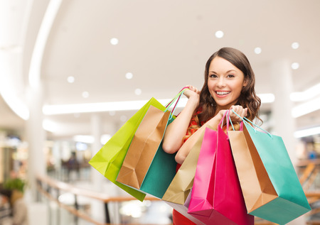 Photo pour happiness, consumerism, sale and people concept - smiling young woman with shopping bags over mall - image libre de droit
