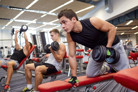 Foto de sport, fitness, lifestyle and people concept - group of men flexing muscles with dumbbells in gym - Imagen libre de derechos