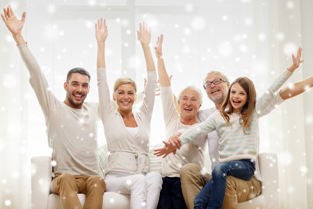Photo pour family, happiness, generation and people concept - happy family sitting on sofa and rising hands at home - image libre de droit