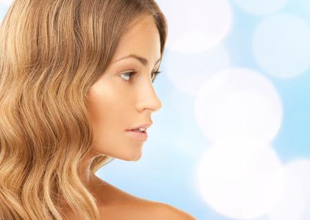 Photo pour beauty, people and health concept - beautiful young woman face over blue lights  - image libre de droit