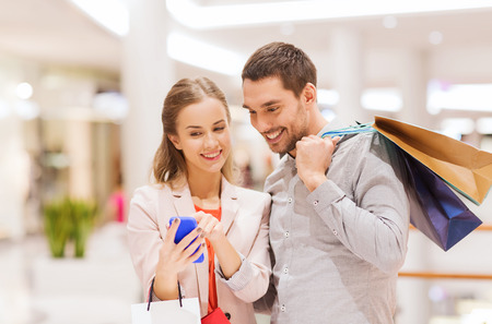 sale, consumerism, technology and people concept - happy young couple with shopping bags and smartphone talking in mall