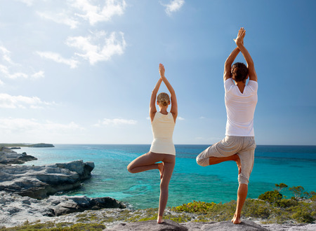 Photo pour fitness, sport, and lifestyle concept - couple making yoga exercises on beach from back - image libre de droit