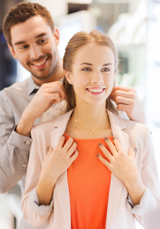 Photo pour sale, consumerism, presents, holidays and people concept - happy couple trying golden pendant on at jewelry store in mall - image libre de droit