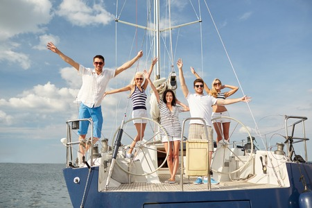Photo pour vacation, travel, sea, friendship and people concept - smiling friends sitting on yacht deck and greeting - image libre de droit