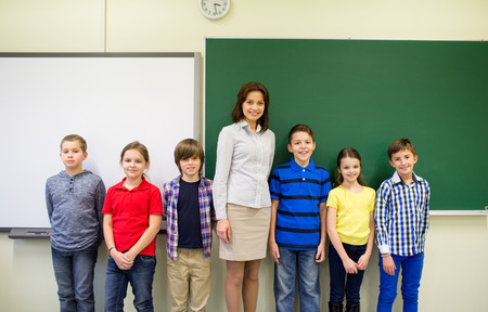 education, elementary, gesture and people concept - group of school kids and teacher in classroom