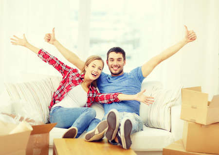 Photo pour moving, home and couple concept - smiling couple relaxing on sofa in new home - image libre de droit