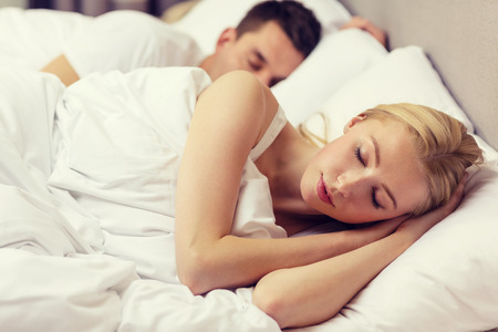 Photo pour hotel, travel, relationships, and happiness concept - happy couple sleeping in bed - image libre de droit