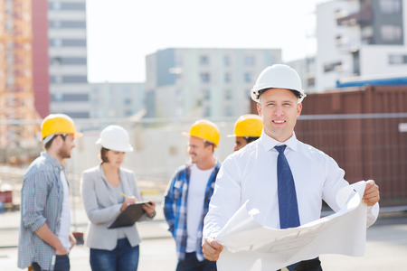 business, building, teamwork and people concept - group of smiling builders in hardhats with clipboard and blueprint outdoors