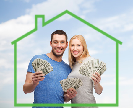 love, home, people and family concept - smiling couple holding dollar cash money over green house and blue sky background
