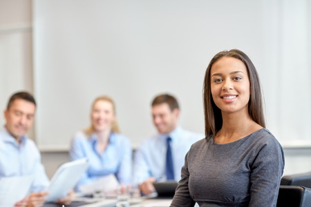 Photo pour business, people and teamwork concept - smiling businesswoman with group of businesspeople meeting in office - image libre de droit
