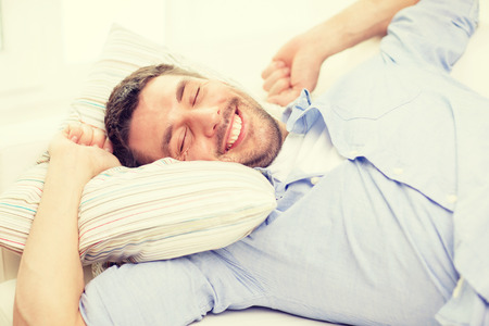home and happiness concept - smiling young man lying on sofa at home