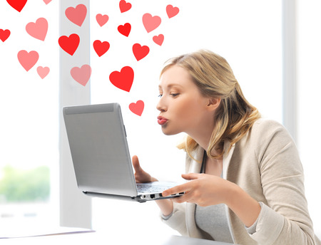 virtual relationships, online dating and social networking concept - woman sending kisses with laptop computer