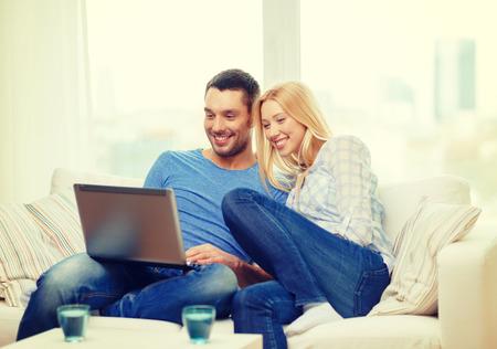 Photo pour love, family, technology, internet and happiness concept - smiling happy couple witl laptop computer at home - image libre de droit