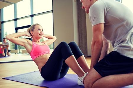 Foto de fitness, sport, training, gym and lifestyle concept - woman with personal trainer doing sit ups in gym - Imagen libre de derechos