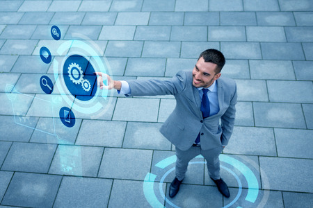 Foto de business, technology and people concept - young smiling businessman pointing finger to settings icon on virtual screen outdoors from top - Imagen libre de derechos