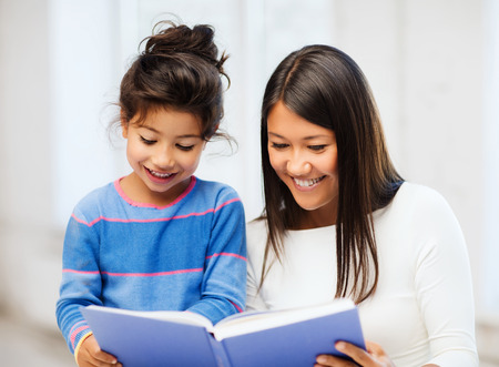 Photo pour family, children, education, school and happy people concept - mother and daughter with book - image libre de droit