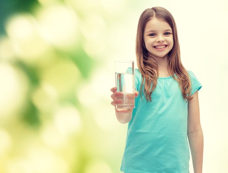 Photo pour health and beauty concept - smiling little girl giving glass of water - image libre de droit