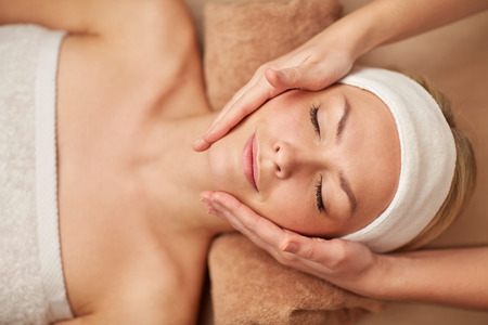 Foto de people, beauty, spa, cosmetology and relaxation concept - close up of beautiful young woman lying with closed eyes having face massage in spa - Imagen libre de derechos