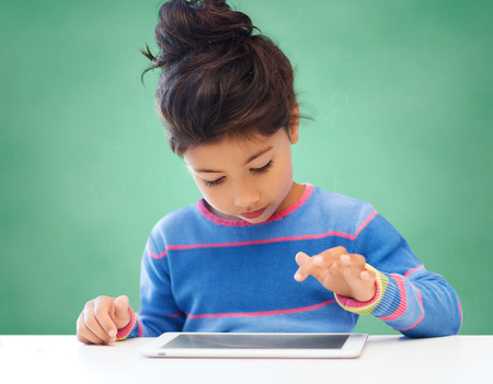 Photo pour education, school, technology and people concept - little student girl with tablet pc over green chalk board background - image libre de droit