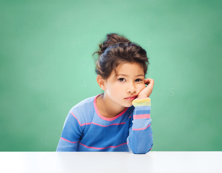 Photo pour education, people, childhood and emotions concept - sad or bored little school girl over green chalk board background - image libre de droit