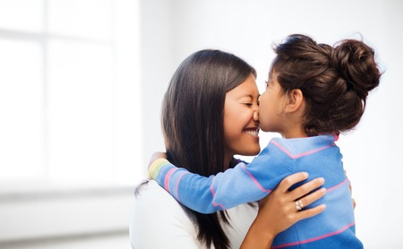 Photo pour family, children and happy people concept - happy little girl hugging and kissing her mother over white room background - image libre de droit