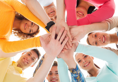 Foto de friendship, youth and people concept - group of smiling teenagers with hands on top of each other - Imagen libre de derechos