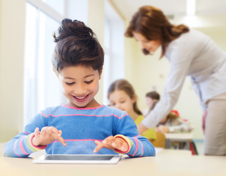 education, elementary school, technology and children concept - happy little student girl with tablet pc over classroom and teacher background