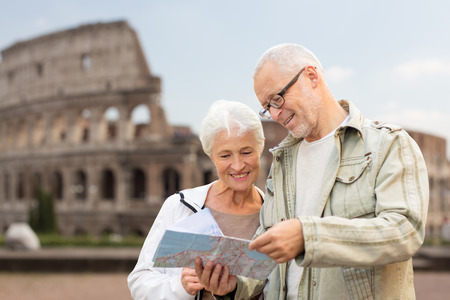 Foto de family, age, tourism, travel and people concept - senior couple with map and city guide on street over coliseum background - Imagen libre de derechos