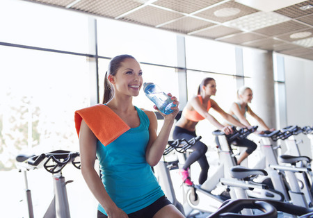 Foto de sport, fitness, lifestyle, equipment and people concept - group of women with water bottle riding on exercise bike in gym - Imagen libre de derechos