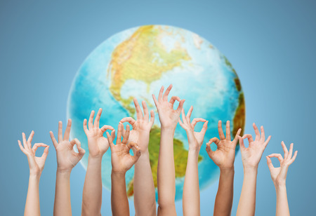 Foto de gesture, people, humanity and community concept - human hands showing ok sign over earth globe and blue background - Imagen libre de derechos