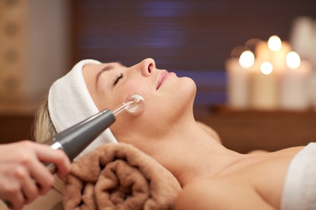 Photo pour people, beauty, spa, cosmetology and technology concept - close up of beautiful young woman lying with closed eyes having face massage by massager in spa - image libre de droit