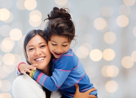 Photo pour people, happiness, love, family and motherhood concept - happy mother and daughter hugging over holiday lights background - image libre de droit