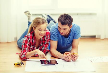 Photo pour repair, building, renovation and home concept - smiling couple looking at tablet pc at home - image libre de droit