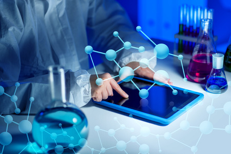 Photo for science, chemistry, medicine, technology and people concept - close up of young female scientist with tablet pc computer making test or research in laboratory - Royalty Free Image