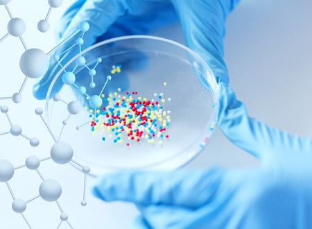 science, chemistry, biology, medicine and people concept - close up of scientist or doctor hands holding petri dish with chemical capsules chemical in laboratory