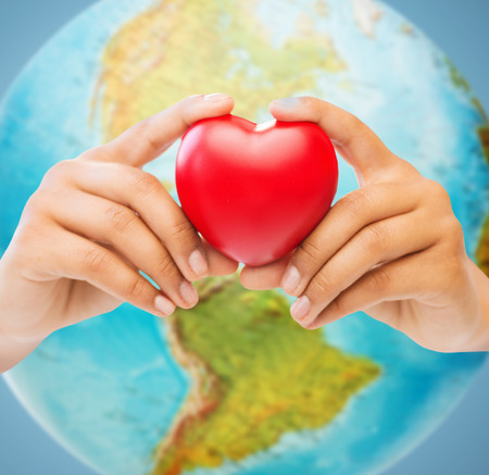 Foto de people, love, health, environment and charity concept - close up of woman hands holding red heart over earth globe and blue background - Imagen libre de derechos